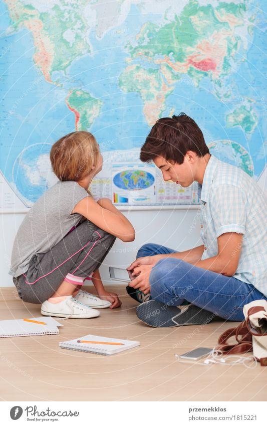 Jugendliche, die durch die Karte im Klassenzimmer sitzen Mensch Mädchen sprechen Lifestyle Junge Schule Denken Computer lernen Papier Studium Bildung Handy