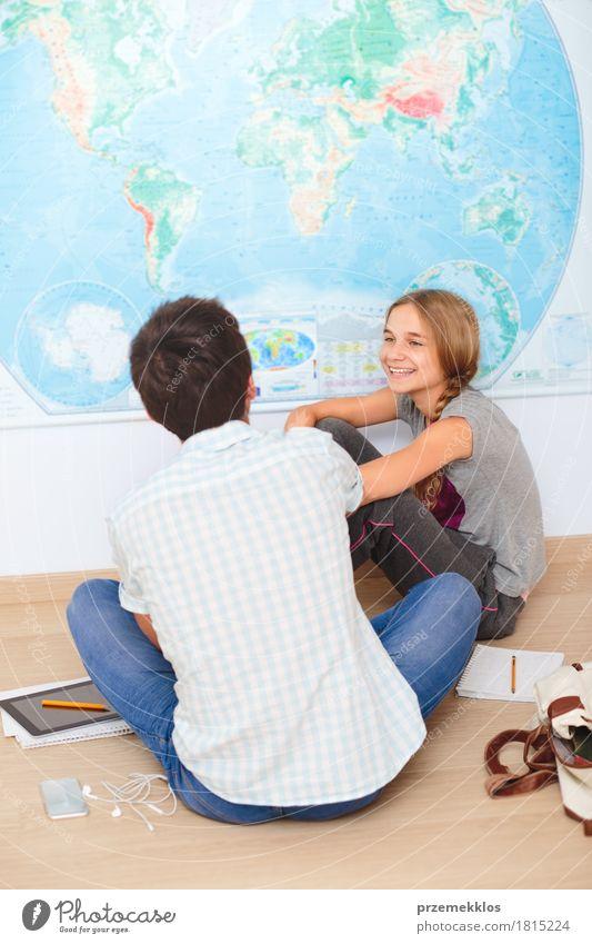 Jugendliche, die durch die Karte im Klassenzimmer sitzen Lifestyle Bildung Schule lernen Klassenraum Schulkind Schüler Studium Student Arbeitsplatz Handy