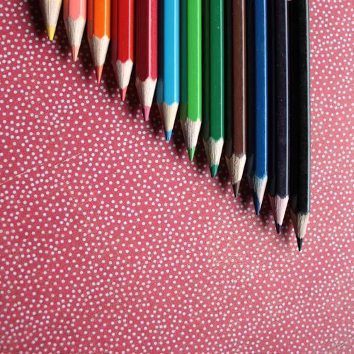Buntstifte liegen auf einem rot-weiß gepunkteten Hintergrund Farbfoto mehrfarbig Innenaufnahme Detailaufnahme Menschenleer Textfreiraum links Textfreiraum unten