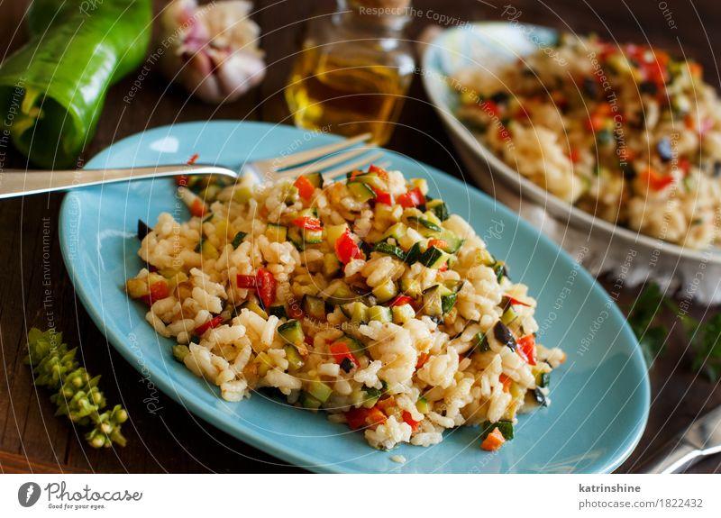 Risotto mit Gemüse Getreide Kräuter & Gewürze Öl Ernährung Mittagessen Abendessen Vegetarische Ernährung Diät Italienische Küche Teller Flasche Gabel Holz