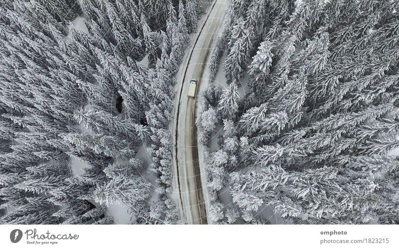 Luftaufnahme einer verschneiten und vereisten Winterstraße mit einem fahrenden Auto darauf Schnee Berge u. Gebirge Natur Landschaft Baum Wald Straße PKW
