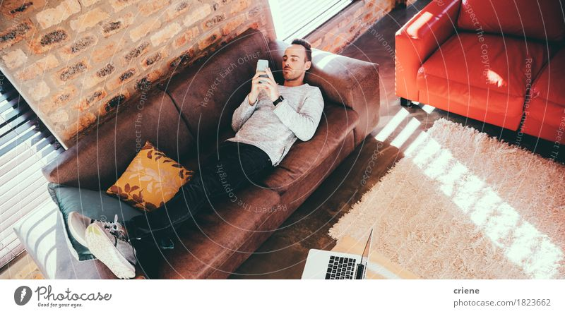Junger erwachsener Mann, der auf das Couchgrasen mit seinem Smartphone legt Lifestyle Erholung Freizeit & Hobby Wohnzimmer Arbeitsplatz Büro Business