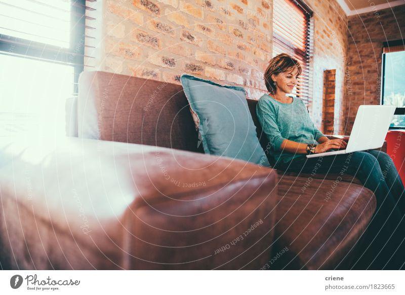 Reife Frau, die auf Couch am modernen Haus sitzt Lifestyle Arbeit & Erwerbstätigkeit Beruf Büro Business Computer Notebook Technik & Technologie Internet Mensch