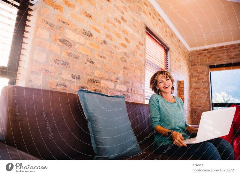 Frau, die den Spaß zu Hause hat, der mit ihrem Laptop auf Couch lacht Lifestyle Freude Arbeit & Erwerbstätigkeit Arbeitsplatz Business Computer Notebook