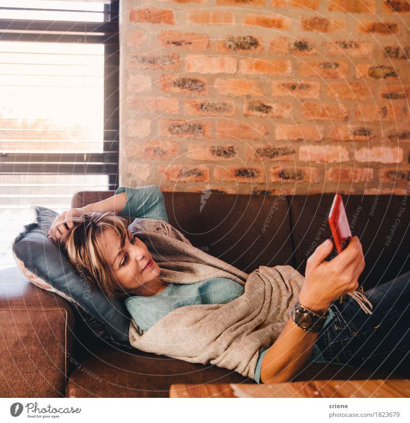 Fällige Frau simst Nachricht mit Smartphone lesen Wohnzimmer Telefon Handy PDA Technik & Technologie Internet Mensch Erwachsene Senior modern bequem reif Texten