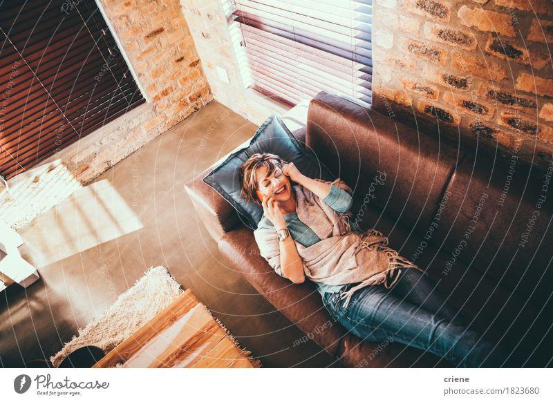 Reife Frau, die zu Hause auf Telefonanruf legt Lifestyle Freude Glück Erholung Freizeit & Hobby Sofa Wohnzimmer sprechen Handy Technik & Technologie