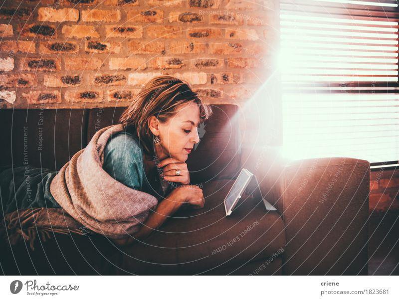 Reife kaukasische Frauenlesezeitung auf ihrer digitalen Tablette Erholung Erwachsene Lifestyle Business Arbeit & Erwerbstätigkeit Freizeit & Hobby modern