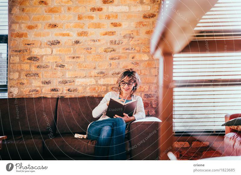 Kaukasische Frau, die ein Buch im Wohnzimmer im modernen Haus liest Lifestyle Freude Freizeit & Hobby lesen Häusliches Leben Wohnung Traumhaus lernen Büro