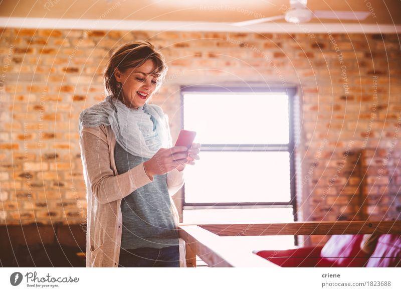 Kaukasische glückliche Frau, die im Wohnzimmer unter Verwendung des Mobiltelefons steht Lifestyle Freude Freizeit & Hobby Telefon Handy PDA