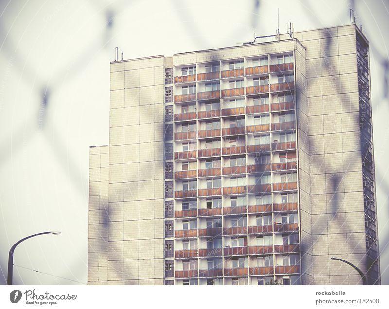 Hochhausansicht durch Maschendrahtzaun Gedeckte Farben Außenaufnahme Tag Stadt Haus Gebäude Architektur Mauer Wand Fassade Balkon alt einfach hoch