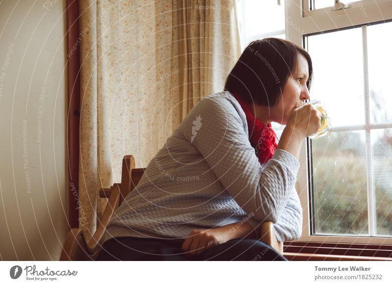 Frau, die durch trinkenden Tee des Fensters aufpasst Einsamkeit Erwachsene Traurigkeit Denken hell nachdenklich warten Idee beobachten weich Stuhl heimwärts