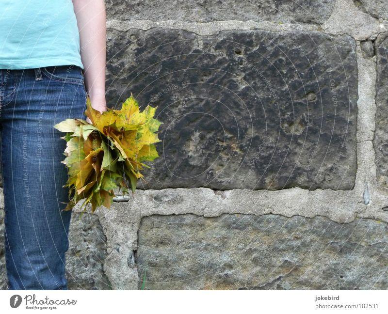 Herbststrauß Mensch blau Blatt gelb Wand feminin Mauer Stein Beine Arme Jeanshose T-Shirt stehen festhalten trocken