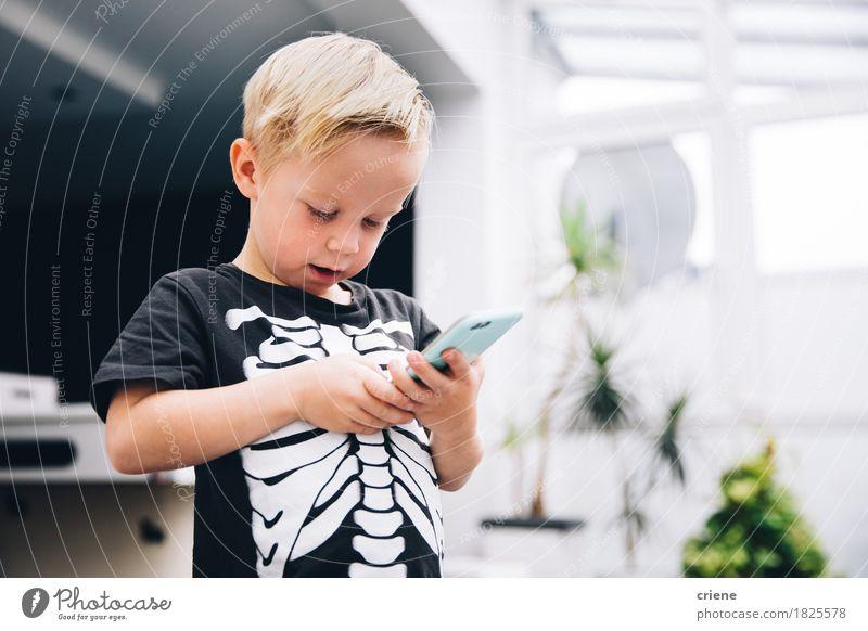 Kleiner Junge im Skeletthemd, das Spiele am intelligenten Telefon spielt Mensch Freude Lifestyle Spielen modern Kindheit Technik & Technologie genießen Internet