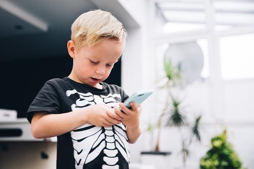 Kleiner Junge im Skeletthemd, das Spiele am intelligenten Telefon spielt Lifestyle Freude Spielen Handy PDA Technik & Technologie Unterhaltungselektronik