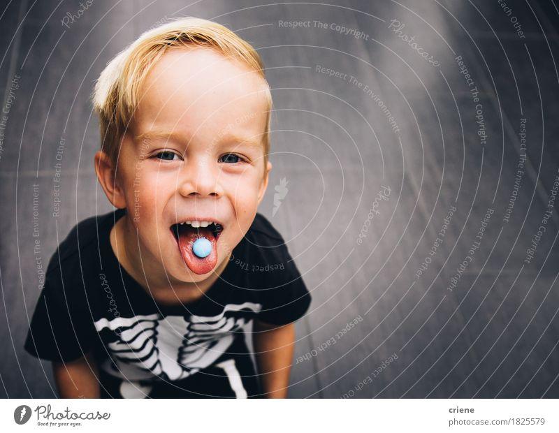 Unverschämter kleiner Junge, der heraus Zunge beim Essen von Bonbons ausdehnt Lebensmittel Süßwaren Lifestyle Freude Kind Kleinkind Kindheit Mund genießen
