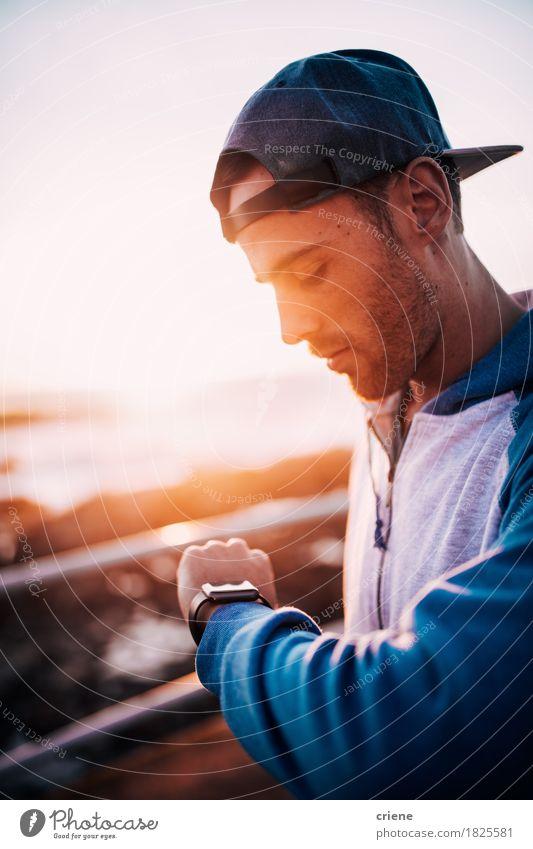 Junger kaukasischer erwachsener Mann, der auf seiner intelligenten Uhr Sonnenuntergang betrachtet Lifestyle Sommer Technik & Technologie Internet Mensch