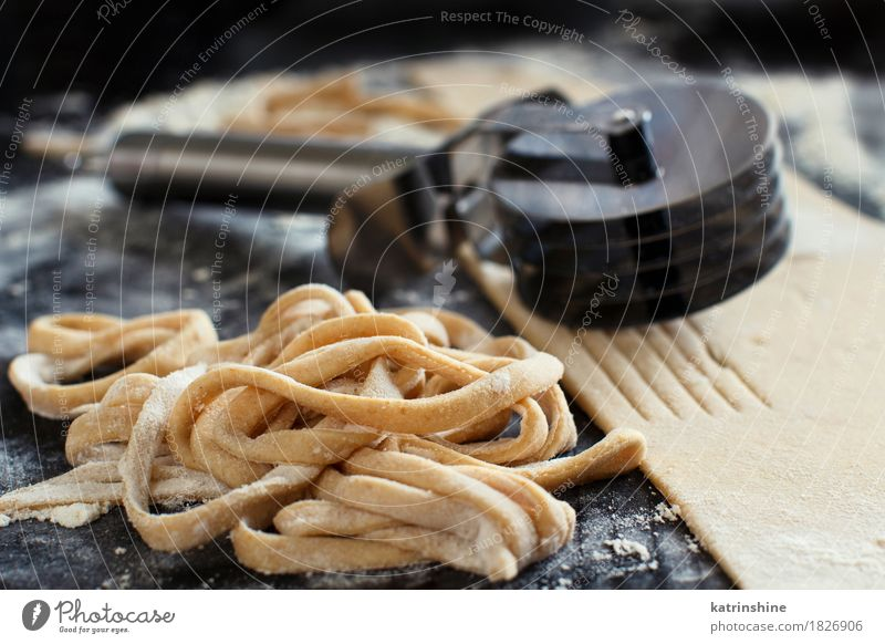 Making hausgemachte Taglatelle mit einer Pasta Rollschneider Teigwaren Backwaren Ernährung Italienische Küche Tisch Werkzeug machen dunkel frisch Tradition