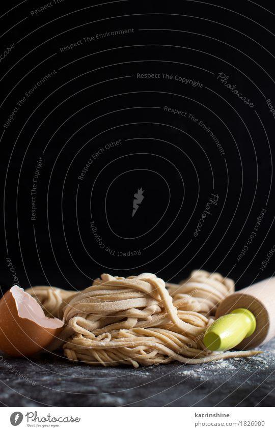 Frische hausgemachte Pasta und Nudelholz Teigwaren Backwaren Vegetarische Ernährung Italienische Küche dunkel frisch gelb Kohlenhydrat Essen zubereiten Mehl
