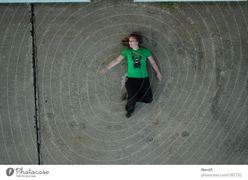 von oben Frau grün Zufriedenheit liegen Boden T-Shirt Gelassenheit Vogelperspektive Betonplatte Betonboden Vor hellem Hintergrund