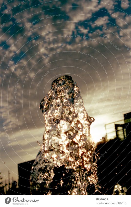 Lichtklumpen Wasserfontäne Springbrunnen Brunnen Sonnenuntergang Gegenlicht Wolken Flüssigkeit nass Wassertropfen frozen ruhig