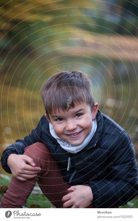 Freude Kind Junge Kindheit Leben 1 Mensch 3-8 Jahre Glück Fröhlichkeit lustig lachen brünett schön Herbst herbstlich See Seeufer Außenaufnahme hockend Oktober
