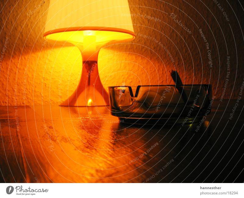 aschenbecher Aschenbecher Lampe Tisch Zigarette Tabak Licht dunkel Häusliches Leben Glas hell Statue Beleuchtung Zigarettenstummel