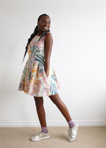 . Raum feminin Frau Erwachsene 1 Mensch Kleid Turnschuh schwarzhaarig langhaarig Zopf Rastalocken Afro-Look beobachten Bewegung drehen Erholung gehen Lächeln