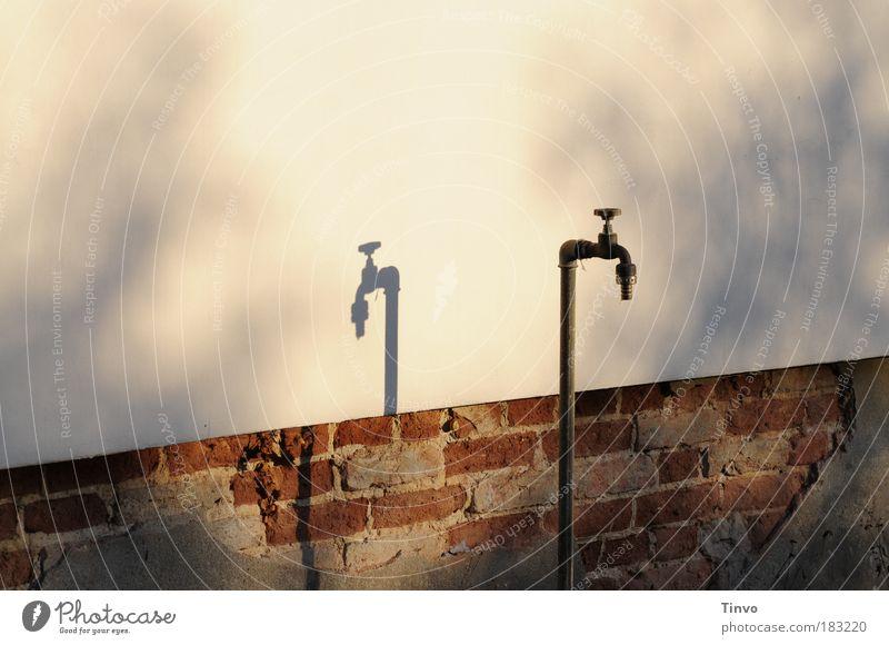Geldhahn Farbfoto Außenaufnahme Menschenleer Textfreiraum oben Abend Licht Schatten Kontrast Mauer Wand alt Armut neu Vergänglichkeit Wandel & Veränderung