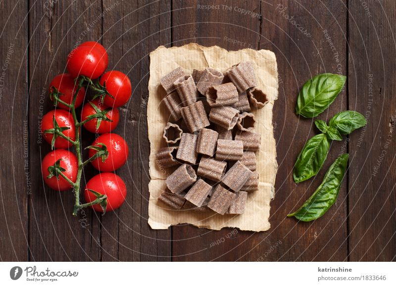 Rohe italienische Teigwaren-, Basilikum- und Kirschtomaten grün rot Blatt dunkel braun Ernährung frisch Tisch Kräuter & Gewürze Gemüse Tradition Backwaren