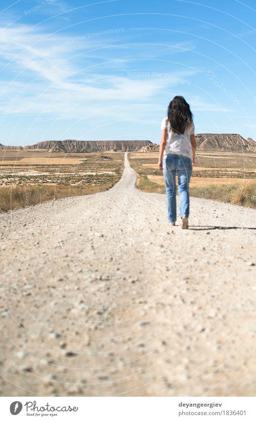 Frau mit den Jeans, die auf wilden Westen gehen Ferien & Urlaub & Reisen Ferne Freiheit Sonne Berge u. Gebirge Mädchen Erwachsene Erde Himmel Horizont Hügel