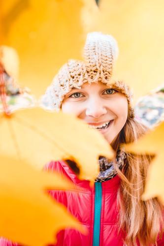 Lächelndes Mädchen, das hinter den unscharfen gelben Herbstblättern steht Glück schön Garten Jugendliche Gesicht 1 Mensch 8-13 Jahre Kind Kindheit Natur Blatt