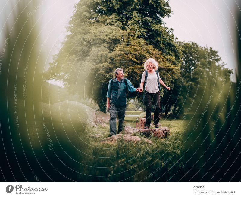 Reifes Paar, das im Urlaub grüne Felder der Wanderrinne kreuzt Mensch Frau Natur Ferien & Urlaub & Reisen Erholung Freude Erwachsene Senior Lifestyle Sport