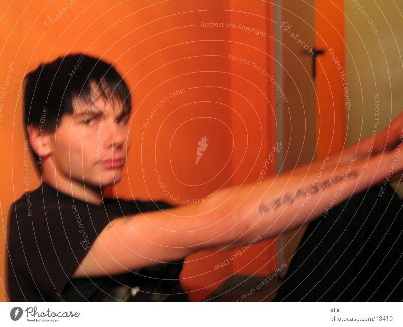unbroken reflection Mann schwarz Traurigkeit orange sitzen Trauer Tattoo Piercing ernst Hardcore Halbtotale
