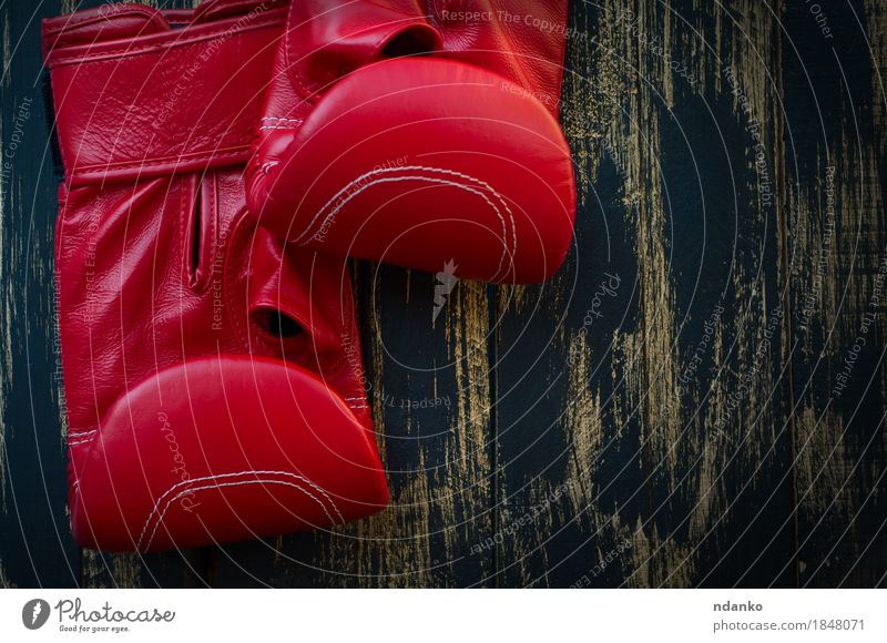 Rote lederne Boxhandschuhe für das Boxen auf einem schwarzen Hintergrund Sport Sportmannschaft Sportveranstaltung Erfolg Paar Leder Ring Handschuhe Holz Fitness