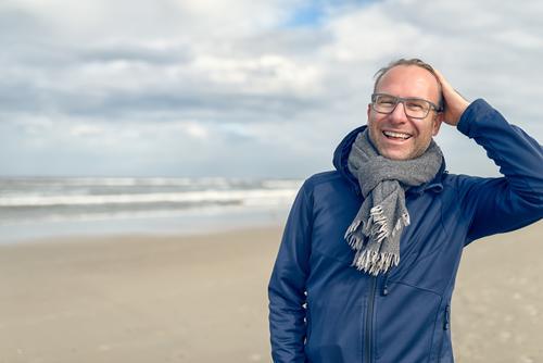 Glücklicher lachender Mann von mittlerem Alter mit Gläsern Mensch Ferien & Urlaub & Reisen Meer Erholung Strand Gesicht Erwachsene Herbst Lifestyle grau