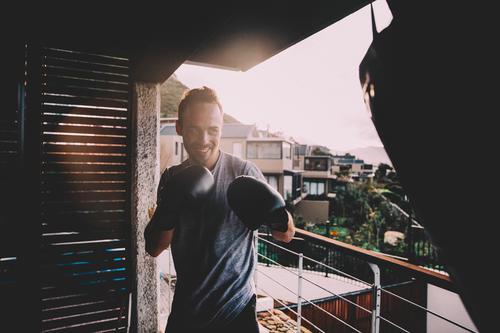 Junger Erwachsener, der zu Hause Boxtraining auf Balkon tut Jugendliche Sommer Junger Mann Freude 18-30 Jahre Lifestyle Sport Wohnung Häusliches Leben