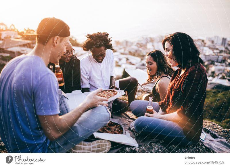 Mutli-ethnische Gruppe, die Pizza und Getränke bei Sonnenuntergang genießt Jugendliche Sommer Freude Essen Lifestyle Feste & Feiern Party Menschengruppe