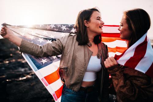 Junge Jugendlichmädchen, die Spaß mit USA-Flagge am Strand haben Lifestyle Freude Ferien & Urlaub & Reisen Tourismus Ausflug Freiheit Junge Frau Jugendliche