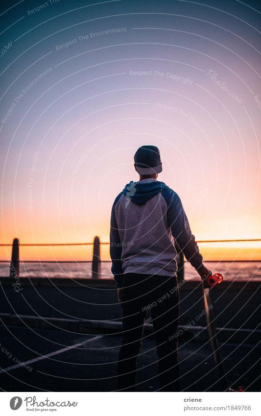Hippie-Kerl, der auf Straße mit dem aufpassenden Sonnenuntergang Longboard steht Lifestyle Stil Freude Freizeit & Hobby Freiheit Meer Sport maskulin Junger Mann