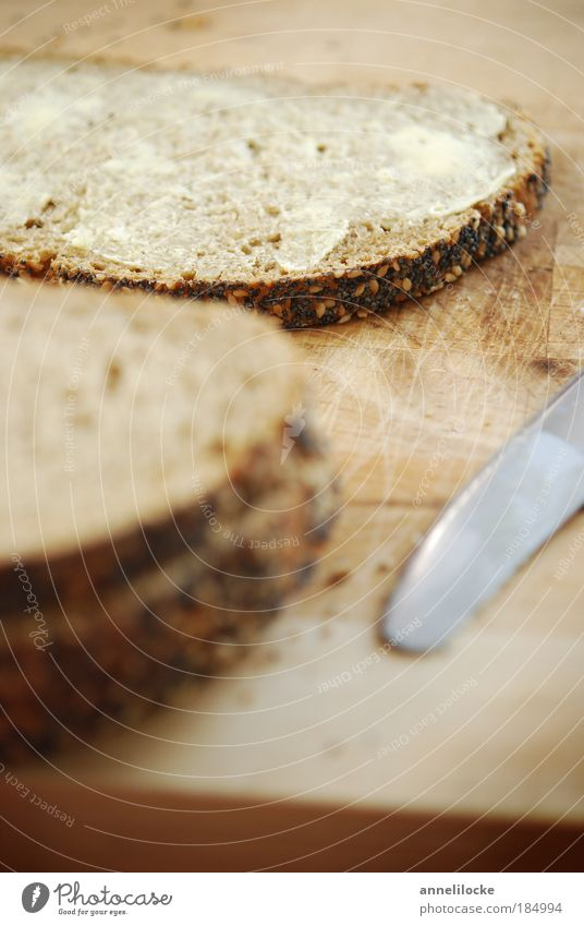 lecker Butterstulle Lebensmittel Brot Mohn Sesam Ernährung Frühstück Abendessen Bioprodukte Vegetarische Ernährung Messer Schneidebrett braun knusprig