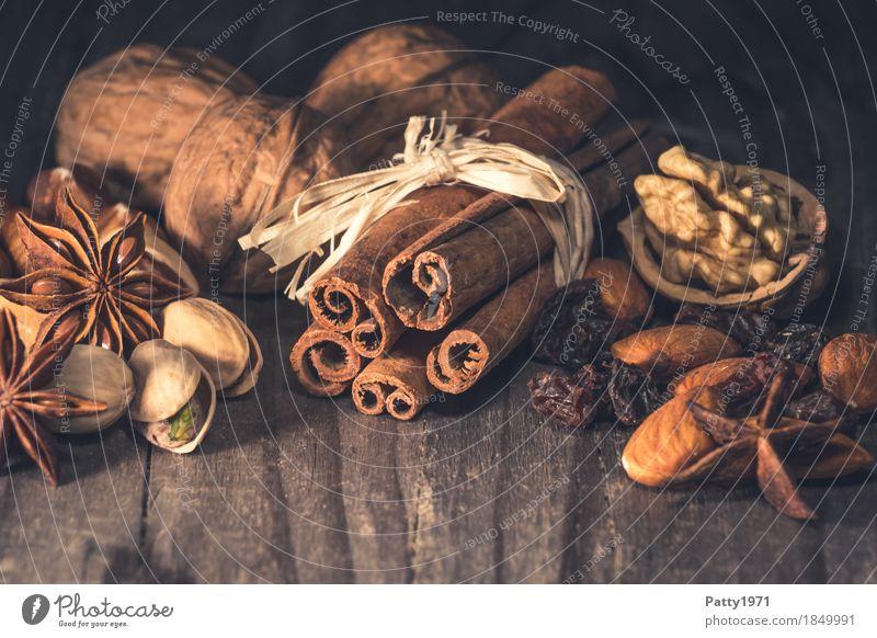 Zimt, Anis, Rosinen und Nüsse liegen auf rustikalem Holztisch. Weihnachtsgewürze. Lebensmittel Frucht Kräuter & Gewürze Walnuss Sternanis Pistazie Mandel