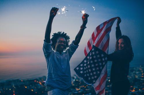 Glückliches Mixed Race Paar feiert mit Wunderkerze und USA-Flagge Lifestyle Freude Ferien & Urlaub & Reisen Tourismus Ausflug Abenteuer Freiheit Sommer