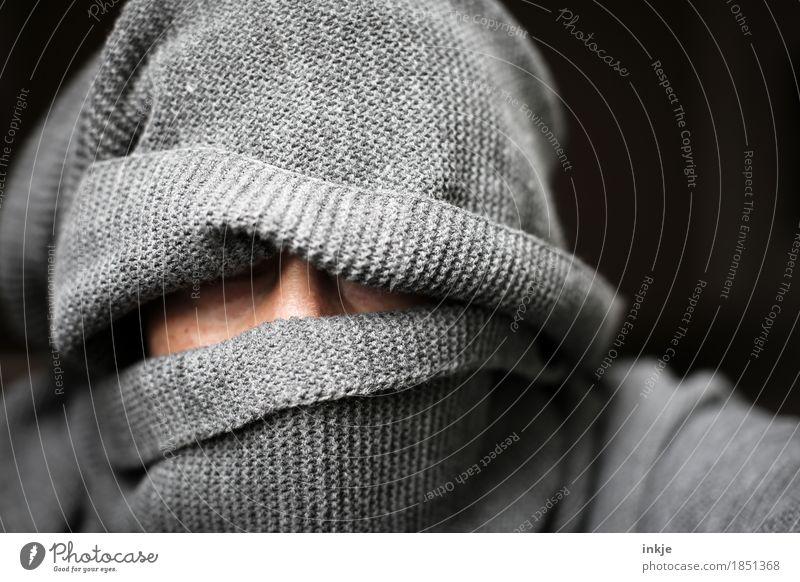 graue Gestalt Mensch Frau Erwachsene Mann Leben Kopf Gesicht 1 Schal Mütze gestrickt bedrohlich dunkel vermummt eingemummt Wollmütze Vor dunklem Hintergrund