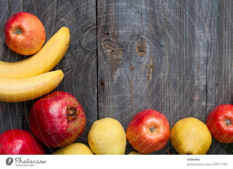 Frucht auf hölzernem Hintergrund: Banane, Apfel, Birne und Granatapfel Lebensmittel Vegetarische Ernährung Lifestyle Herbst Holz frisch saftig grau essbar
