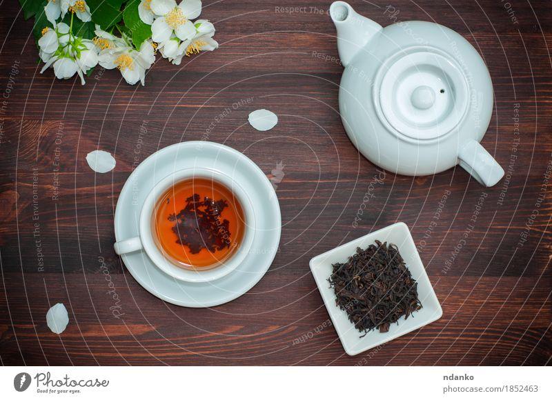 Schwarzer Tee mit Jasmin in einer weißen Schale auf einem braunen Holztisch Kräuter & Gewürze Frühstück Abendessen Asiatische Küche Getränk trinken Heißgetränk