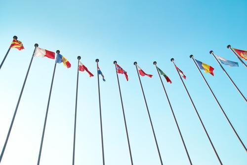 Reihe der europäischen Flaggen Menschengruppe Himmel Wolkenloser Himmel Sonnenlicht Wind Streifen Fahne fliegen Zusammensein groß blau mehrfarbig gelb grün rot