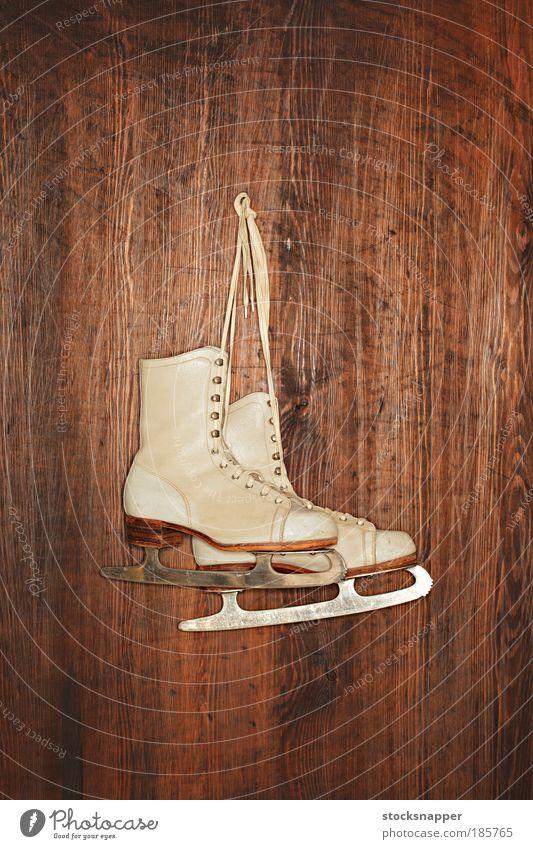 Alte Schlittschuhe Schlittschuhlaufen Eis alt weiß altehrwürdig abgenutzt Leder Schuhe Sport erhängen Wand hölzern paarweise