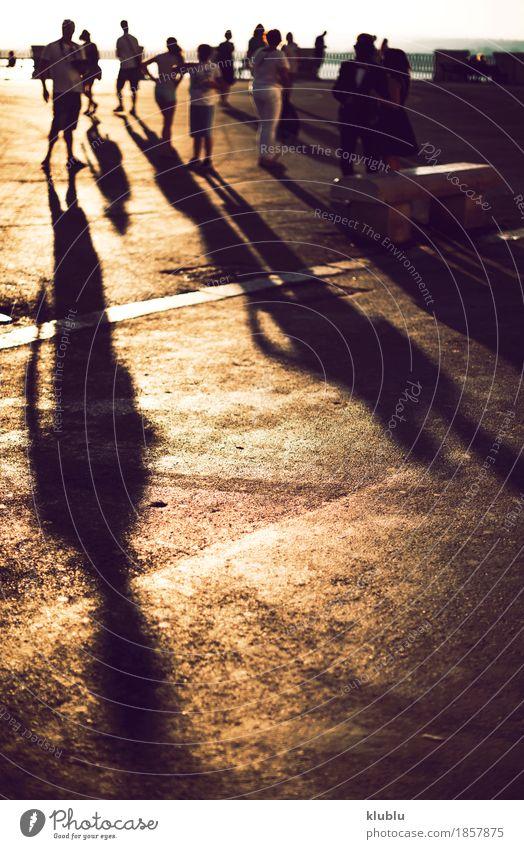 Schatten von Leuten, die am Sonnenuntergang gehen kaufen Leben Ferien & Urlaub & Reisen Mensch Fuß Menschengruppe Stadt Fußgänger Straße Stein lang schwarz