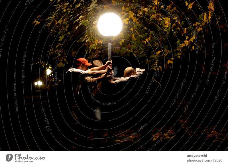 Es leuchtet (Farbe) Mensch Mann Baum dunkel hell festhalten erleuchten grell