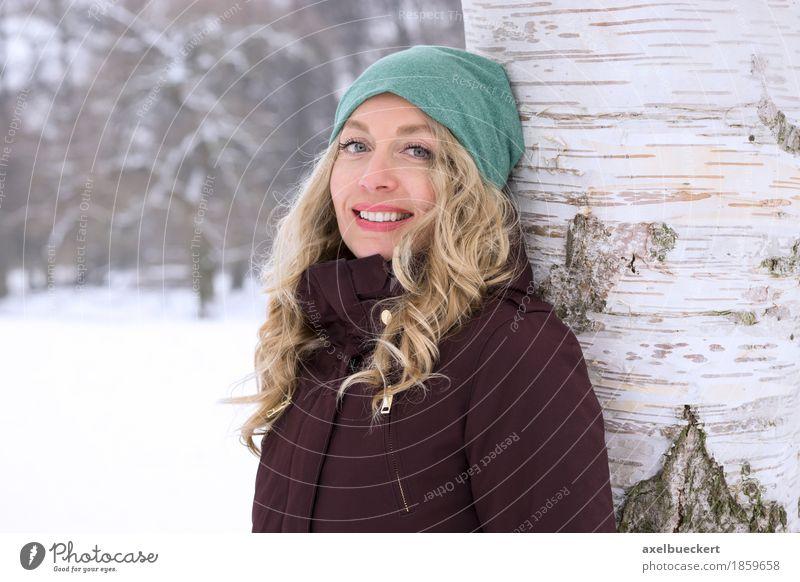 happy woman leaning against tree in winter Mensch Frau Natur Ferien & Urlaub & Reisen Jugendliche Junge Frau Baum Landschaft Erholung Freude Winter Wald